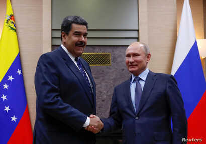 FILE PHOTO: Russian President Vladimir Putin, right, shakes hands with his Venezuelan counterpart Nicolas Maduro during a meeting at the Novo-Ogaryovo state residence outside Moscow, Russia Dec. 5, 2018.