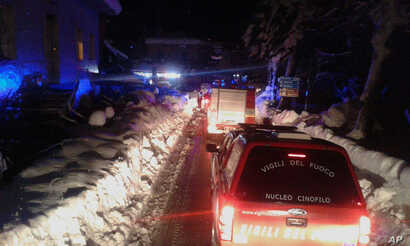 Firefighters vehicles make their way to the hotel hit by an avalanche in Farindola, Italy, Jan. 19, 2017.