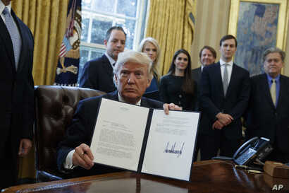 President Donald Trump shows his signature on an executive order on the Keystone XL pipeline, Jan. 24, 2017, in the Oval Office of the White House.