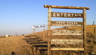 FILE - This Sept. 9, 2012 file photo shows the entrance to the Pine Ridge Indian Reservation in South Dakota, home to the Oglala Lakota tribe.  (AP Photo/Kristi Eaton)