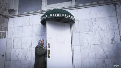 """A woman stands below the awning of an Ahmadi mosque in Brooklyn, New York. """"Love for all, hatred for none,"""" the banner reads. (R. Taylor/VOA)"""
