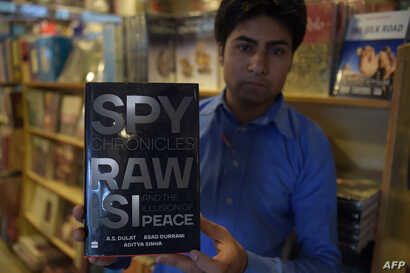 "FILE - A Pakistani salesman shows ""The Spy Chronicles: RAW, ISI and the Illusion of Peace,"" co-written by Asad Durrani, a retired Pakistani army officer, at a bookstore in Islamabad, May 30, 2018."