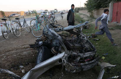 FILE - Afghans gather at the site of a suicide car bomb attack in the Qarabagh district of Kabul, Afghanistan, Sept. 12, 2015. The attacker targeted an Afghan lawmaker's son, who survived. On Sept. 23, 2017, officials confirmed that scores of Talib...