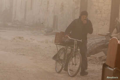 A man covers his face from dust as he walks with a bicycle after a strike on the rebel held besieged al-Shaar neighborhood of Aleppo, Syria, Nov. 26, 2016.