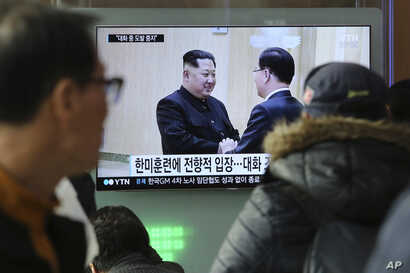 People watch a TV screen showing North Korean leader Kim Jong Un, left, meeting with South Korean National Security Director Chung Eui-yong in Pyongyang, North Korea, at the Seoul Railway Station in Seoul, South Korea, March 7, 2018.