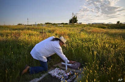 In this July 14, 2018, file photo, Kenny Still Smoking touches the tombstone of his 7-year-old daughter, Monica, who disappeared from school in 1979 and was found frozen on a mountain, as he visits her grave on the Blackfeet Indian Reservation in Bro...