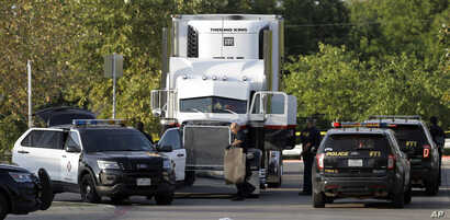 San Antonio police officers investigate the scene where immigrants were found dead in a tractor-trailer loaded outside a store in stifling summer heat, July 23, 2017, in San Antonio.