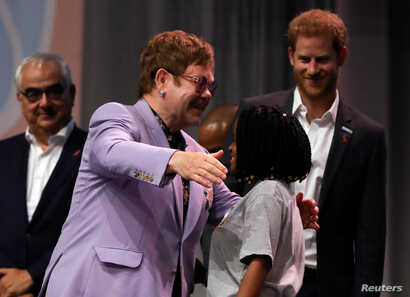 "British musician Elton John embraces a participant as Britain's Prince Harry looks on during a panel ""Breaking barriers of inequity in the HIV response"" during the 22nd International AIDS Conference (AIDS 2018), the largest HIV/AIDS-focused meeting i..."