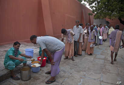 In this Nov. 13, 2017 photo, homeless people who were picked from the streets line up for food at Anand Ashram, a shelter home for male beggars in Hyderabad.