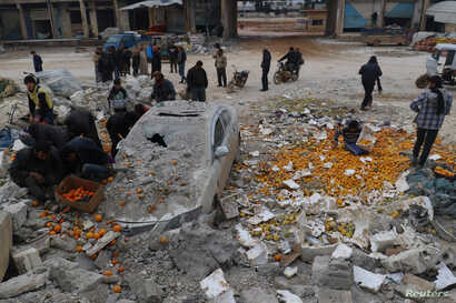 People collect scattered oranges amidst rubble after an airstrike on a market in rebel-held Maarrat Misrin in Idlib province, Syria, Jan. 14, 2017.