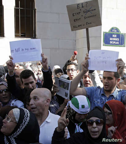 """Muslims holding signs saying """"not in my name"""" gather in front of the Paris Mosque after Friday prayers Sept. 26, 2014 to pay tribute to Herve Gourdel, a French mountain guide who was beheaded by an Algerian Islamist group, and to protest extremist ta..."""