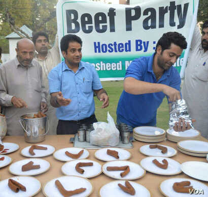 "Rashid Ahmed, in gray Pathani suit, offering beef kabab at his ""Beef Party"" in his official residence in Srinagar on 7 October, 2015.  (Pirzada Firdous Ahmad/VOA)"