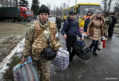 A member of the Ukrainian armed forces assists local residents onto a bus to flee the military conflict, in Debaltseve, eastern Ukraine, Feb. 6, 2015.
