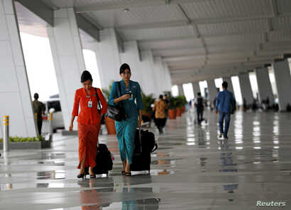 Garuda Indonesia flight attendants arrive at Terminal 3 Ultimate on the first day of its operations for domestic flights at Soekarno-Hatta Airport in Jakarta, Indonesia, Aug. 9, 2016. Female Muslim flight attendants now will have to wear headscarves...