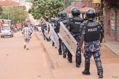 Anti-riot police walk the streets of Kampala, Uganda, Sept. 21, 2017, searching for protesters against the lifting the constitutional age limit for presidents.