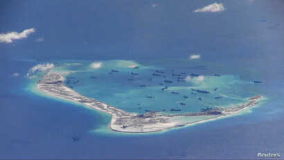 Chinese dredging vessels are purportedly seen the waters around Mischief Reef in the disputed Spratly Islands in the South China Sea in this video image taken by a P-8A Poseidon surveillance aircraft provided by the U.S. Navy, May 21, 2015.