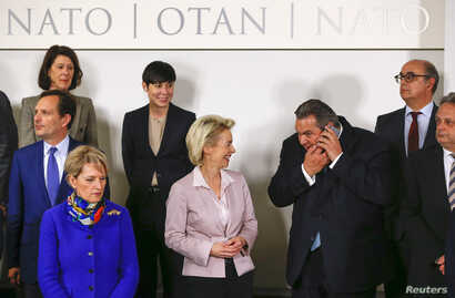 German Defense Minister Ursula von der Leyen (C) talks with Greek Defense Minister Panos Kammenos (2nd R) at a family photo during a NATO defense ministers meeting at the Alliance's headquarters in Brussels, Belgium Feb. 10, 2016.