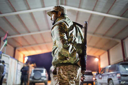 FILE -  Libyan military soldier stands guard at the entrance of a town, 110 kilometers (68 miles) from Sirte, Libya.