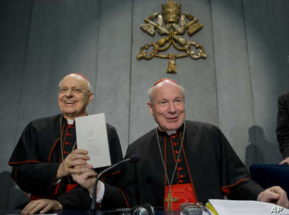 Cardinals Lorenzo Baldisseri, left, and Christoph Schoenborn show a copy of the post-synodal apostolic exhortation ' Amoris Laetitia ' (The Joy of Love) during a press conference at the Vatican, April 8, 2016.