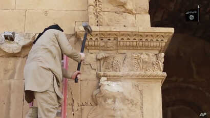 This image from a video posted April 3, 2015, on a website frequently used by Islamic State shows a militant hammering at a face on a wall in Iraq's ancient city of Hatra.