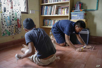 Christian Burmese refugees fix the linoleum floor of their classroom in Kuala Lumpur, Malaysia, March 11, 2017. An Associated Press analysis suggests that the people hurt most by President Donald Trump's planned deep cuts in refugee visas are from My...