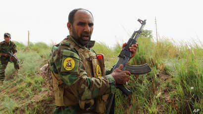FILE - Iraqi Shiite Hezbollah Brigade militiamen take combat positions in the front line against the Islamic State group in Khalidiya, 100 kilometers (60 miles) west of Baghdad, Iraq.