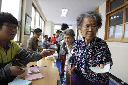FILE - Elderly women wait to cast their ballots in local elections at a polling station in Nonsan, South Korea, June 4, 2014. In South Korea, 100 working-age people fund the social benefits for 37 citizens.