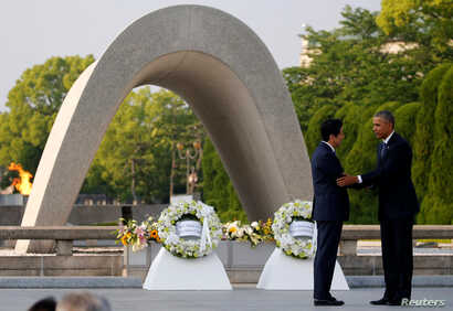 U.S. President Barack Obama (R) puts his arm around Japanese Prime Minister Shinzo Abe after they laid wreaths in front of a cenotaph at Hiroshima Peace Memorial Park in Hiroshima, Japan. May 27, 2016.