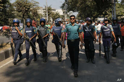 Bangladeshi policemen guard the scene as activists campaigning for capital punishment for war criminals protest a nationwide strike called by the main Islamist party Nov. 23, 2015, in Dhaka, Bangladesh.