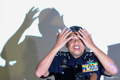Malaysia's Royal Police Chief Khalid Abu Bakar demonstrates to the media during a news conference regarding the apparent assassination of Kim Jong Nam, the half-brother of the North Korean leader, at the Malaysian police headquarters in Kuala Lumpur,...