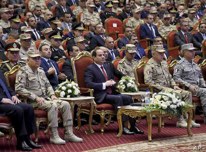 In this photo released by the Egyptian president's office, Egyptian President Abdel Fattah el-Sissi, center, attends a conference commemorating the country's martyrs, in Cairo, March 15, 2018. Up for re-election in less than two weeks, Egypt's presid...