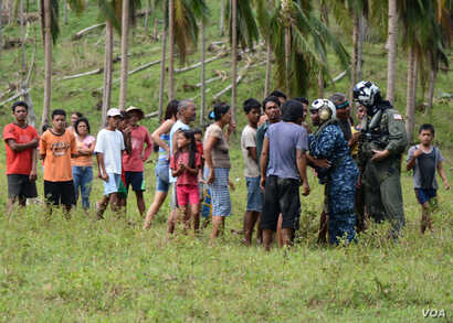 U.S. military personnel speak with Philippine citizens affected by super typhoon Haiyan while delivering relief supplies, Ormoc City, Philippines, Nov. 18, 2013. (U.S. Navy)