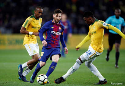 Barcelona Lionel Messi (L) plays the ball during a friendly match between Barcelona v Mamelodi Sundowns for the Mandela Centenary Trophy at FNB Soccer Stadium in Johannesburg, South Africa, May 16, 2018.