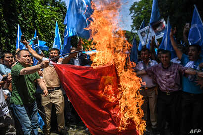 FILE - Supporters of the mostly Muslim Uighur minority and Turkish nationalists burn a Chinese flag during a protest to denounce China's treatment of ethnic Uighur Muslims during a deadly riot on July 2009 in Urumqi, in front of the Chinese consulate...