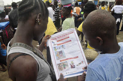 Liberian children read a leaflet with guidelines to protect the community from the Ebola virus,  in Monrovia, Liberia, Oct. 13, 2014.