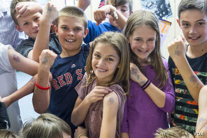 Students and their teacher show temporary tattoos they wear made from the drawing of a letter from Safiyo Noor Hassan, a student in Dadaab Refugee Camp. Fifth graders at Valley Peaks Elementary School participate in a Letters of Hope project in Bould...