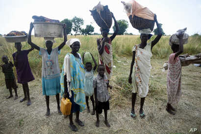 Women stand with their children and belongings in rebel held Bauw village in Koch county of South Sudan's Unity state, Sept. 25, 2015.
