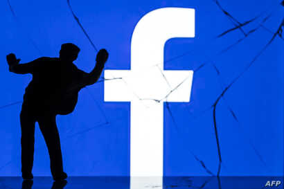 This photograph taken on May 16, 2018, shows a figurine standing in front of the logo of social network Facebook on a cracked screen of a smartphone in Paris.