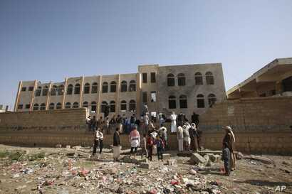 People gather at a school damaged by Saudi-led airstrikes in Sanaa, Yemen,, July 20, 2015.