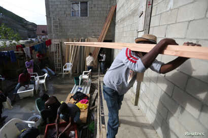 """A Haitian migrant carries wood to build a house in a neighborhood know locally as """"Haitian Villa,"""" Feb. 25, 2017. Some 3,500 Haitians reportedly are now in the border cities of Tijuana and Mexicali."""