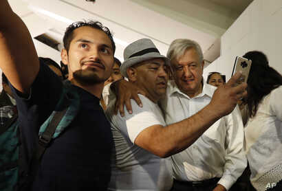 Mexican President Andres Manuel Lopez Obrador, center right, poses for selfies with travelers as he arrives for his commercial flight to Mexico City, at the airport in Guadalajara, Mexico, March 9, 2019.