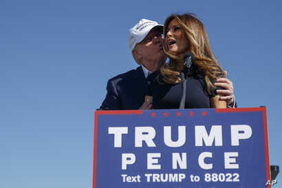 Republican presidential candidate Donald Trump kisses his wife, Melania, during a campaign rally in Wilmington, N.C., Nov. 5, 2016.