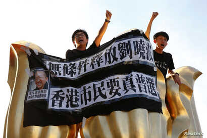 Pro-democracy activists chant slogans on the Golden Bauhinia Square, a gift from China at the 1997 handover, during a protest a day before Chinese President Xi Jinping is due to arrive for the celebrations, in Hong Kong, China, June 28, 2017.