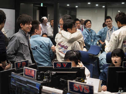 In this photo provided by the Japan Aerospace Exploration Agency, staff of the Hayabusa2 Project react as they confirm Hayabusa2 made a maneuver at the control room of the JAXA Institute of Space and Astronautical Science in Sagamihara, near Tokyo, F...