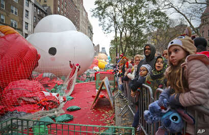 Crowds gather to see giant character balloons being inflated the night before their appearance in the 92nd Macy's Thanksgiving Day parade, Nov. 21, 2018, in New York.