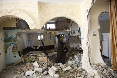 Palestinian woman inspects  the home of Ehab Maswada that was demolished by the Israeli army in the West Bank city of Hebron, Thursday, March 31, 2016.