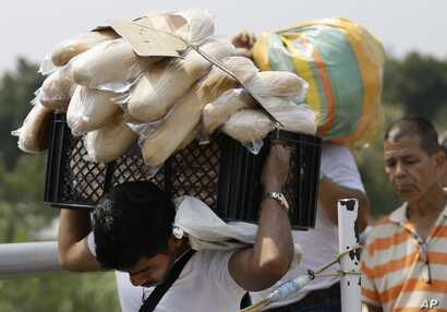 A Venezuelan man carries a crate filled with bread back to his country, in La Parada, on the outskirts of Cucuta, Colombia, on the border with Venezuela, Feb. 4, 2019.
