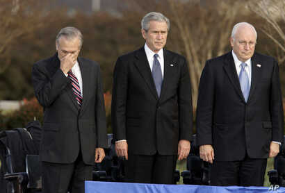 FILE - Secretary of Defense Donald Rumsfeld, left, pauses as President George W. Bush, and Vice President Dick Cheney participate in Rumsfeld's farewell ceremony at the Pentagon in Washington, Dec. 15, 2006.