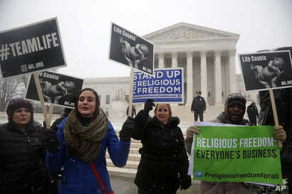 Demonstrators participate in a rally in front of the Supreme Court in Washington, Tuesday, March 25, 2014, as the court heard oral arguments in the challenges of President Barack Obama's health care law requirement that businesses provide their femal...
