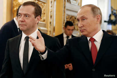 Russian President Vladimir Putin and Prime Minister Dmitry Medvedev walk after the president delivered his annual state of the nation address at the Kremlin in Moscow, Dec. 1, 2016.